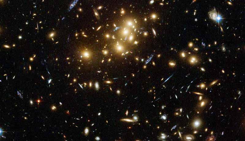 CL 0024+17 galaksi kümesi. Bu küme, etkileşim halinde olan binlerce gökadanın bir araya gelmesiyle oluşmuştur. Bu arada öyle iç içe göründüklerine bakmayın, her birinin arasında milyonlarca ışık yılı mesafe var.